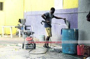It's business as usual for Kemar, an employee from the Ultimate Car Care and Sports Bar is washing the car mats using a pressure pump machine. | JamaicaObserver.com
