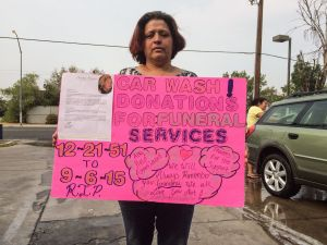 Evangelina Quintanilla and her family wash cars in Central Fresno to help pay for her mother's cremation. (Kerry Klein/KQED)