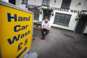Joshua Carney sits outside his pub and the car wash that operates outside. | Witney Gazette