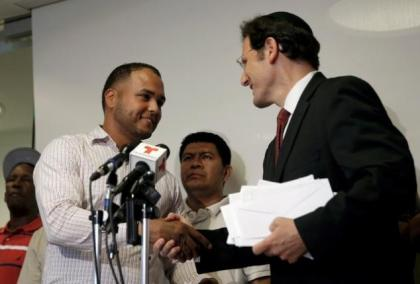 Arenson delivers a check to Rodriguez at news conference in New York